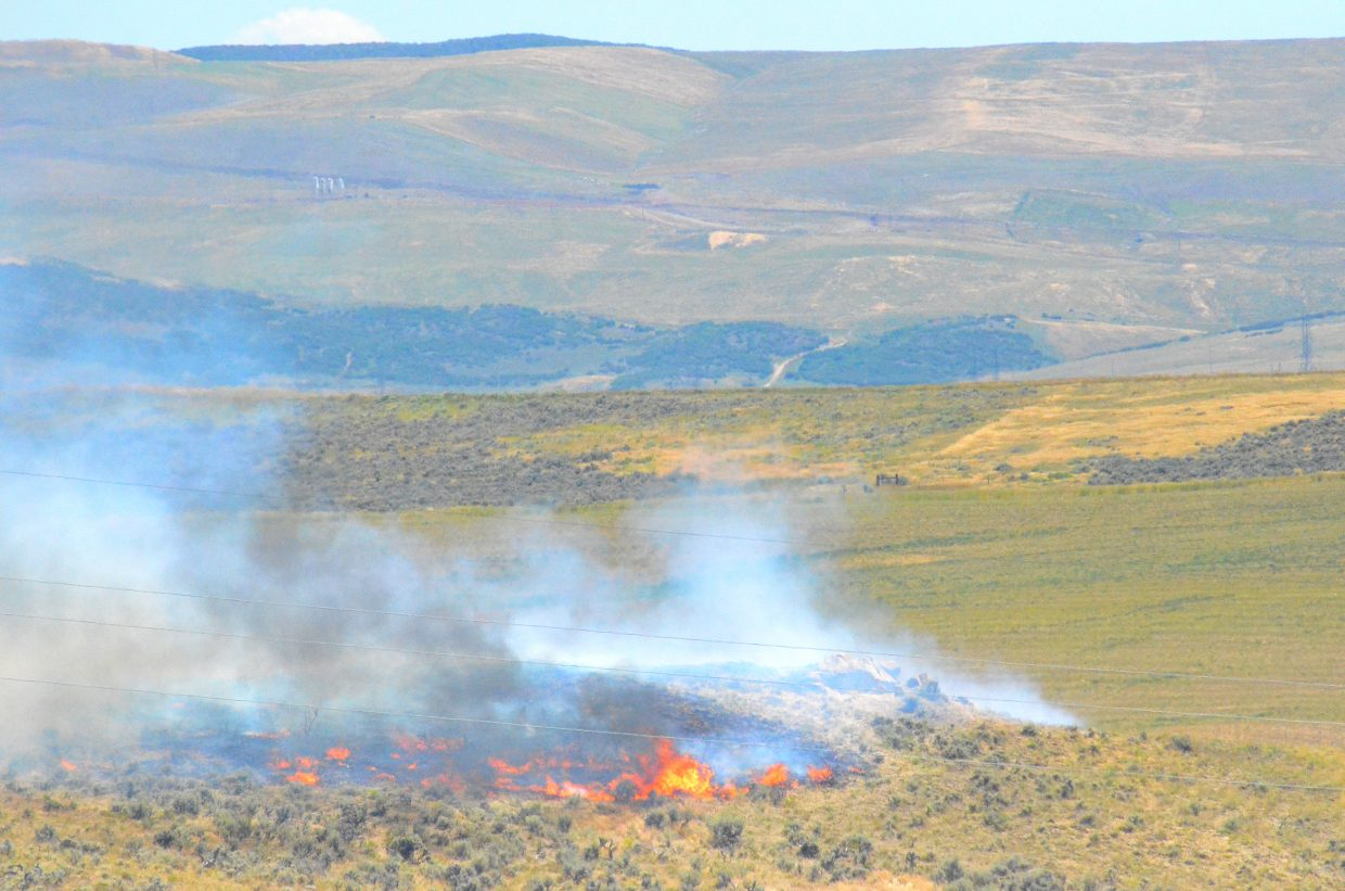 Flames engulf sage brush and dry grasslands near the bypass Thursday afternoon.