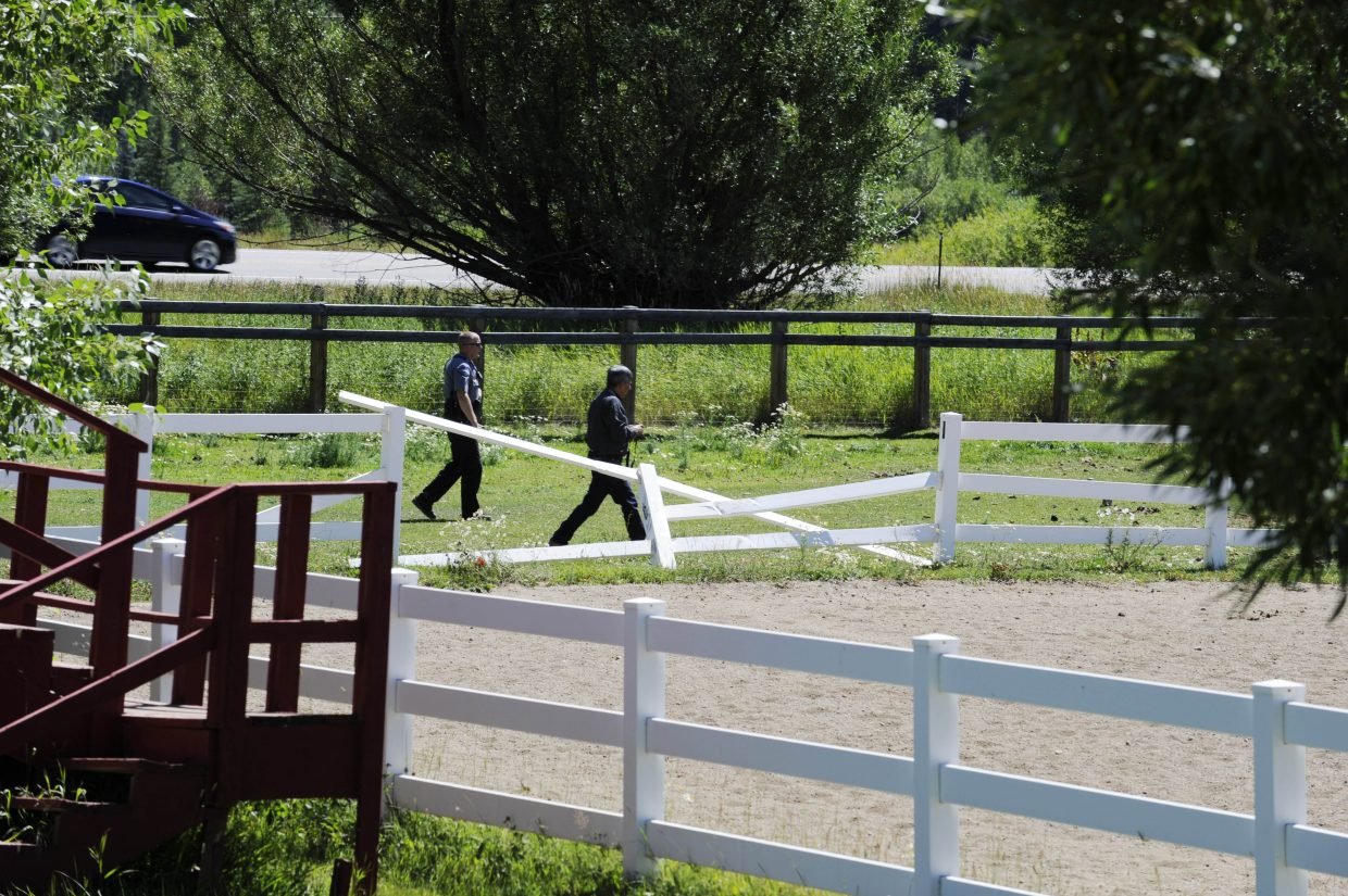 Routt County Sheriff's Office deputies take pictures of a fence damaged during a pursuit that ended at Saddle Mountain Ranch on Thursday.