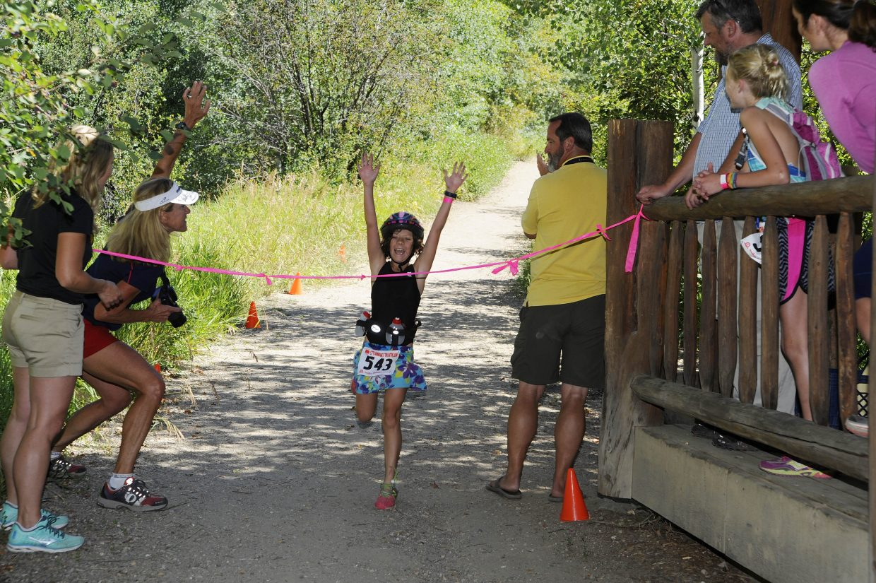 Natalia Craig, 10, passes the finish line Thursday during the Old Town Hot Springs youth triathlon.