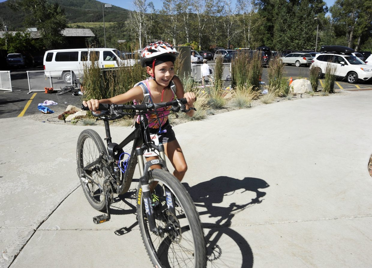 Makyla Kusy, 11, transitions to her bike Thursday during the Old Town Hot Springs youth triathlon.