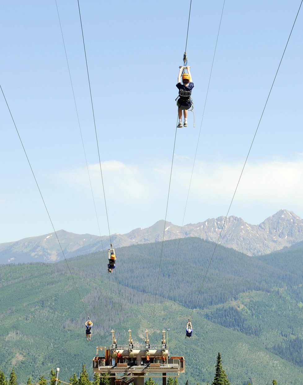 People ride down the zip lines at Vail's Epic Discovery.