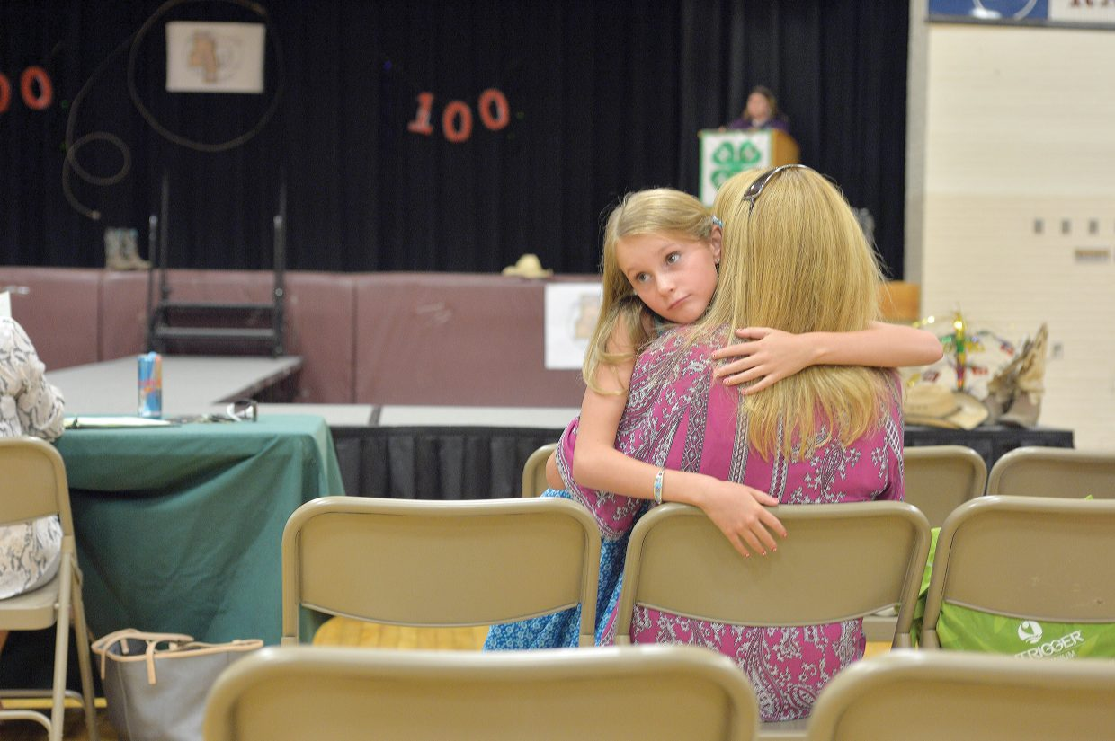 Nine-year-old Taylor Graham hugs her mom, Rhonda, after competing in the Exhibit Day Fashion Show on Friday afternoon. Young 4-H members who spent their summer creating clothing in the sewing program got a chance to show off their work to judges and an audience.