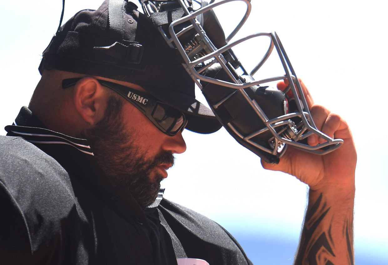 Tony Mauro pulls his umpire's face mask over his United States Marine Corps sunglasses Wednesday during the Triple Crown youth baseball tournament in Steamboat Springs. Mauro is one of nearly a dozen veterans with disabilities serving as umpires at this week's tournament.