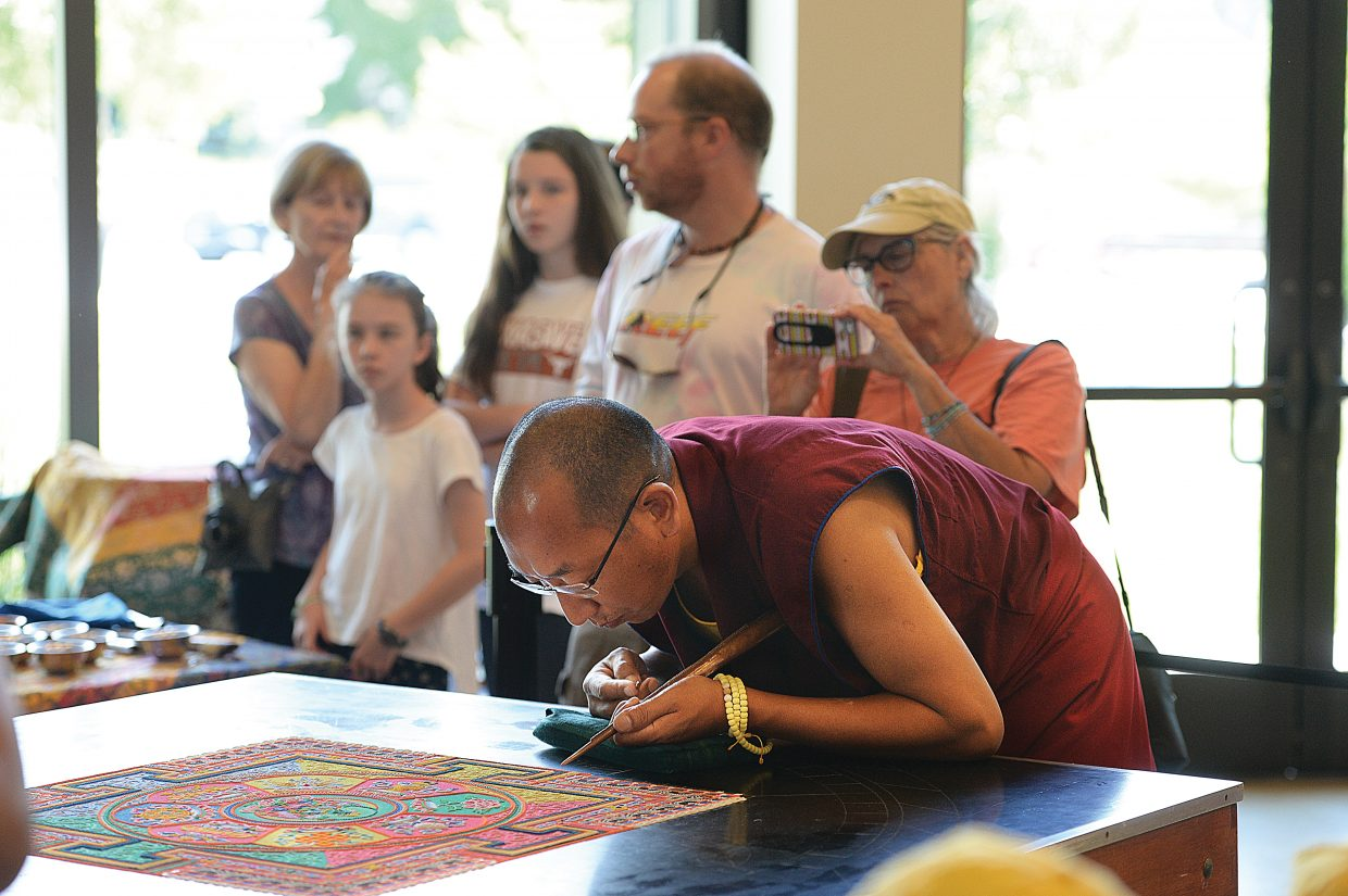 Monk Tsering Phuntsok works on the mandala at the Bud Werner Memorial Library on Friday morning. This is the third day the monks from the Drepung Loseling monastery have been in Steamboat Springs. Work on the mandala will continue today, and Sunday from 10 a.m. until 6 p.m. There will be a closing ceremony Sunday evening at 7 p.m.