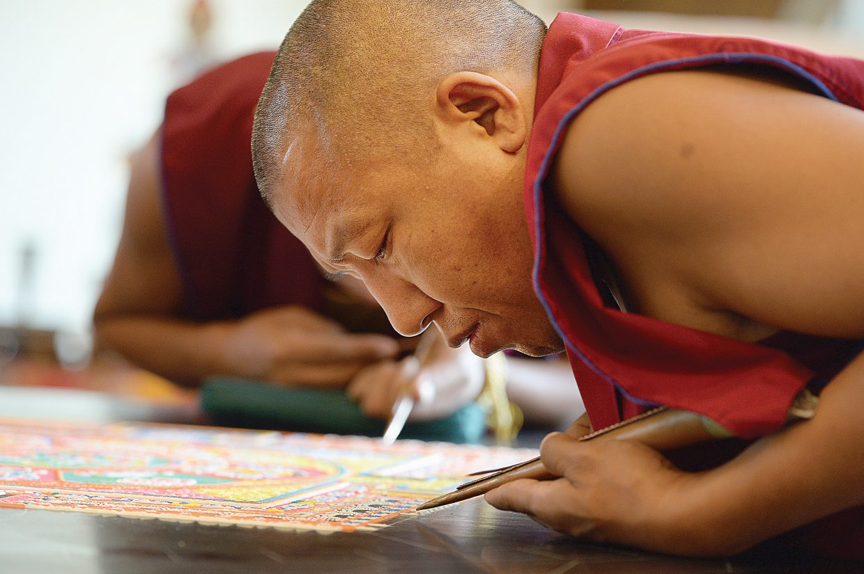 Monk Nyima Tsering Tamang, of the Drepung Loseling Monastery, works to form a mandala image at the Bud Werner Memorial Library on Friday morning.