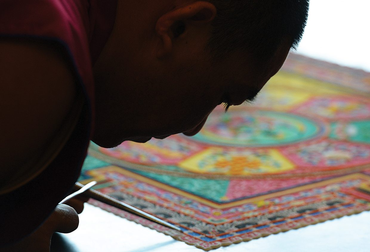 Monk Lobsang Yarphel works on the fine details of the mandala at the Bud Werner Library. This is the third day the monks from the Drepung Loseling monastery have been in Steamboat Springs. Work on the mandala will continue today, and Sunday from 10 a.m. until 6 p.m. There will be a closing ceremony 7 p.m. Sunday.
