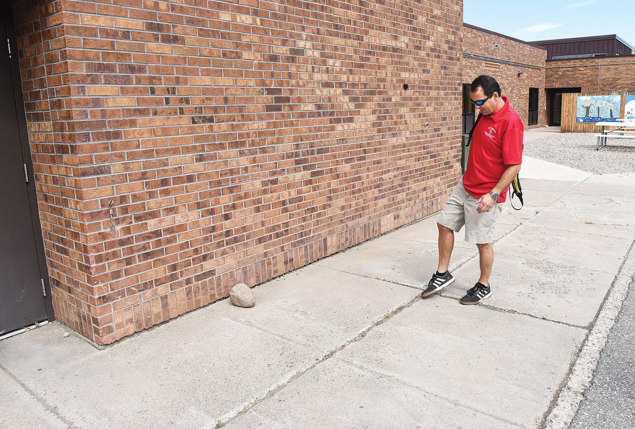Director of Maintenance, Operations and Transportation Pascal Ginesta shows an area of worn cement outside Strawberry Park Elementary in August 2015 which is out of compliance with state and federal codes. New sidewalks, new parking lot pavement and paved fire access around the school are part of the district's long list of needed capital improvements.