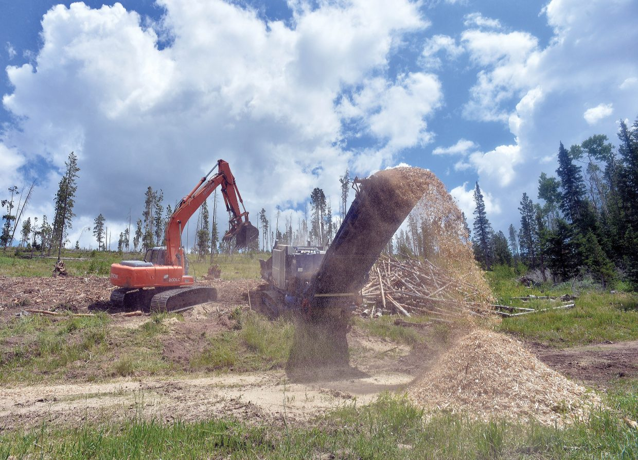 Ty Shearer, of Confluence Energy, uses an excavator to load timber into a chipper in a timber sale area of Gore Pass. The chips are then trucked to a plant in Kremmling where they are used to produce several products including wood pellets.
