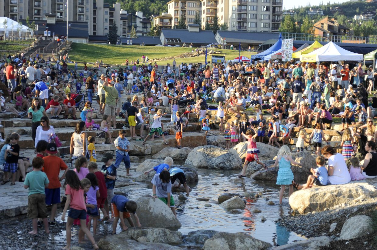 "People gather at the promenade at the base of the Steamboat Ski Area to enjoy music and wade in Burgess Creek. The ""beach"" is in the background near the staircase to Torian Plum Plaza."