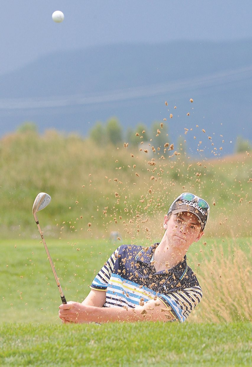 Steamboat Springs High School golfer Drew Williamson chips out of the bunker at the Haymaker Golf Course in Steamboat Springs on Monday afternoon. Williamson is one of the returning members of this year's high school golf team, which will tee off Thursday at Battlement Mesa.