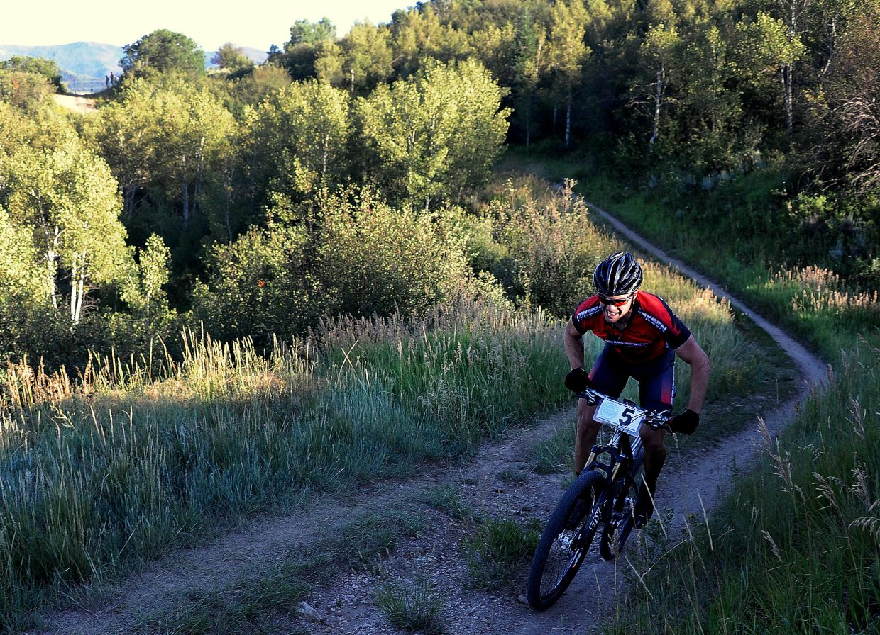 Brad Bingham works his way up one of the final slopes of Wednesday's Town Challenge mountain bike race on Emerald Mountain. He won the event after the first finisher was disqualified for taking a wrong turn.