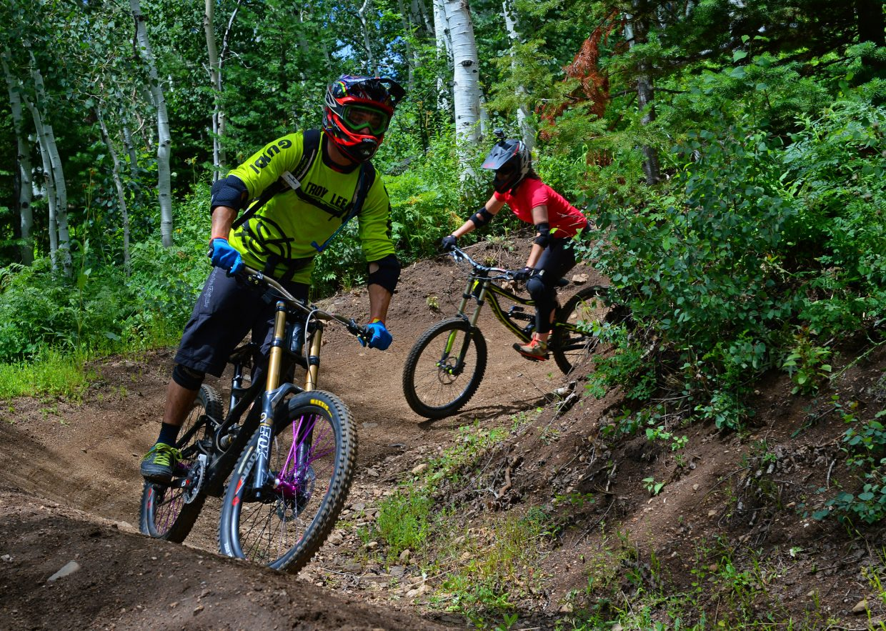 Steamboat Bike Park instructor Tim Price leads Nicole Miller through a banked turn on Rustler Ridge, a blue downhill trail in the Steamboat Bike Park.