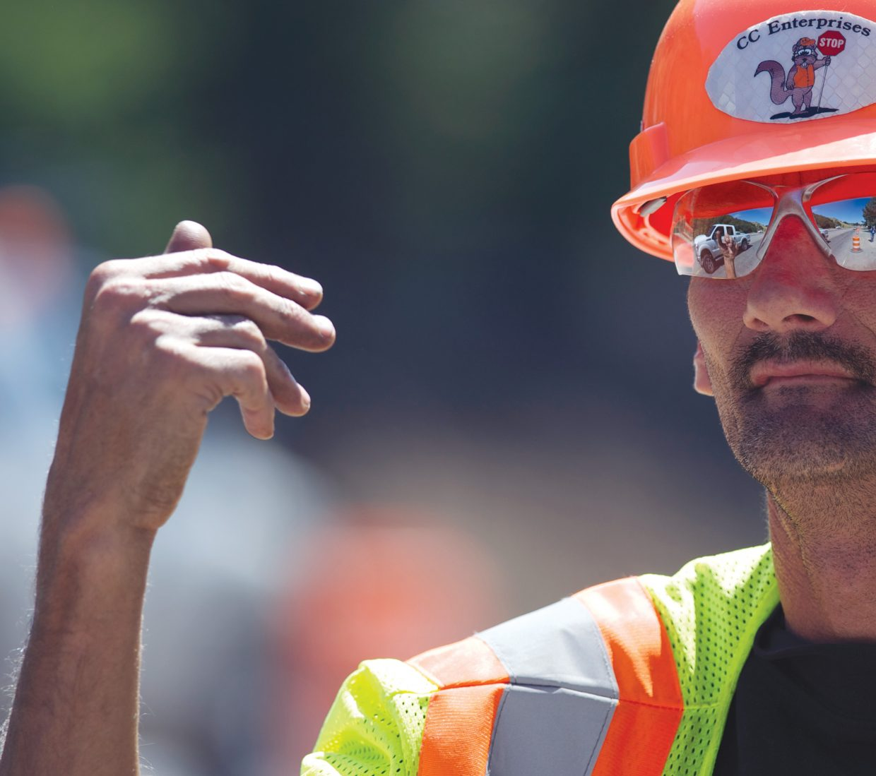 Traffic is reflected in Jerry Speicher's sunglasses as he directs traffic along Lincoln Avenue on Friday morning. A major construction and paving project has frustrated many motorist in the Steamboat area the past few days, and the end is still not in sight.