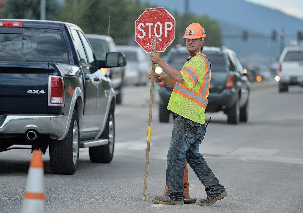 Levy Knight holds up traffic at Anglers Drive and U.S. Highway 40 on Friday evening. Construction work on the roads surrounding Steamboat Springs has slowed traffic, frustrating drivers.