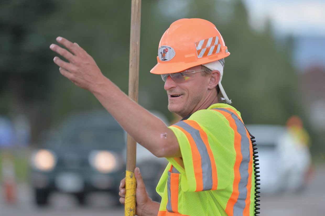 Levy Knight holds up traffic at Anglers Drive and U.S. Highway 40 on Friday evening. Construction work on the roads surround Steamboat Springs has slowed traffic, frustrating drivers.