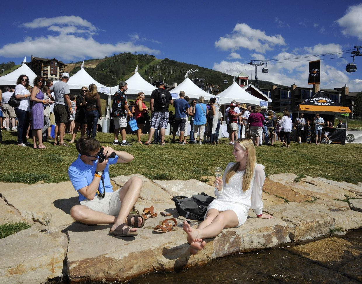 Charlie Aspden and Lauren Widmaier take pictures along Burgess Creek on Saturday during the Steamboat Wine Festival.