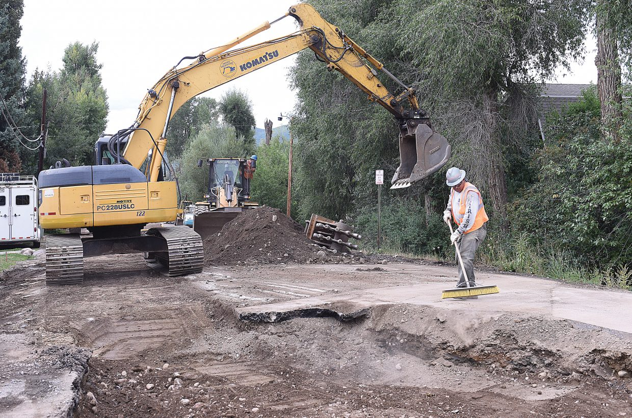 Jose Gonzales uses a broom to clean dirt off the street at Sixth and Pine streets, near where Native Excavating is replacing a water main in downtown Steamboat Springs. Crews have been working on the project for the past month.