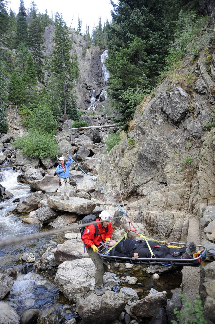 Routt County Search and Rescue volunteers, from left, Russ Sanford and Jay Bowman hoist out mock patient Emily Hines from Fish Creek Falls on Tuesday while the group trained with ropes.