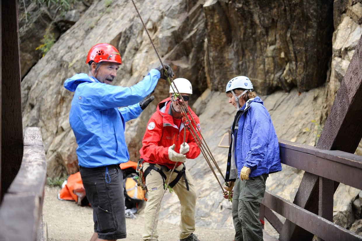Routt County Search and Rescue volunteers, from left, Bill Murphy, Dan Gilchrist and Kristia Check-Hill hoist a rope while training Tuesday at Fish Creek Falls.