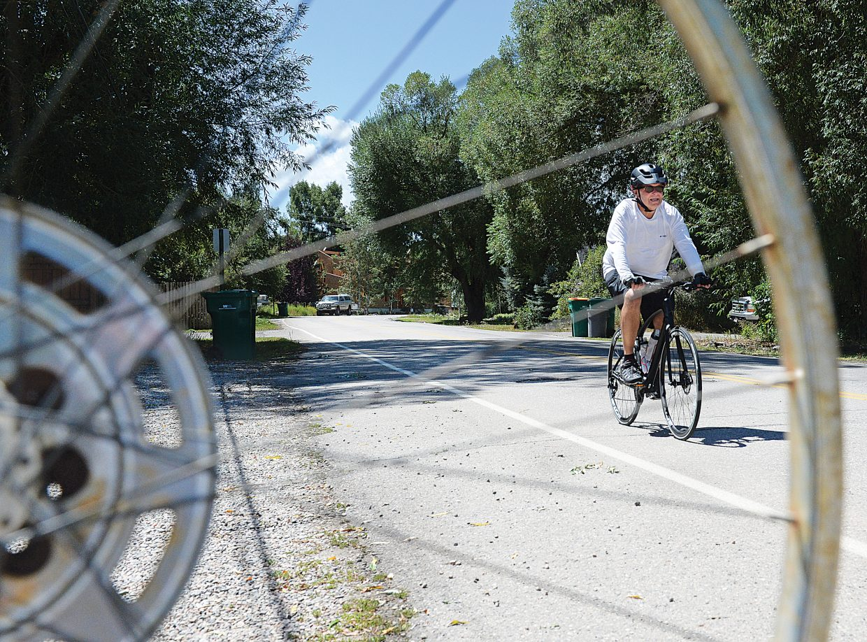 Cyclist Michael Prindible rides past a mail box with an old bike wheel attached to it as he makes his way along River Road Wednesday afternoon. Mild summer weather had plenty of people thinking about getting outside Wednesday afternoon.