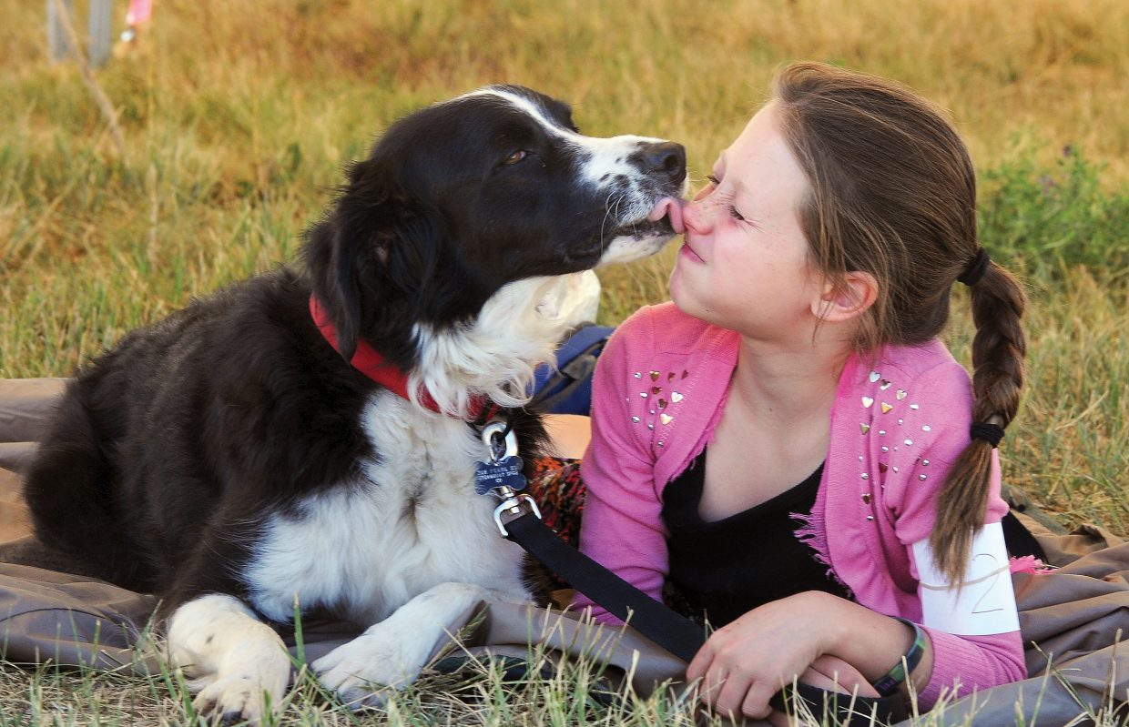 Norah Pietras gets a kiss from Poncho during the Routt County Fair dog show Tuesday morning. The show is the highlight of the summer for members of the 4-H dog program.