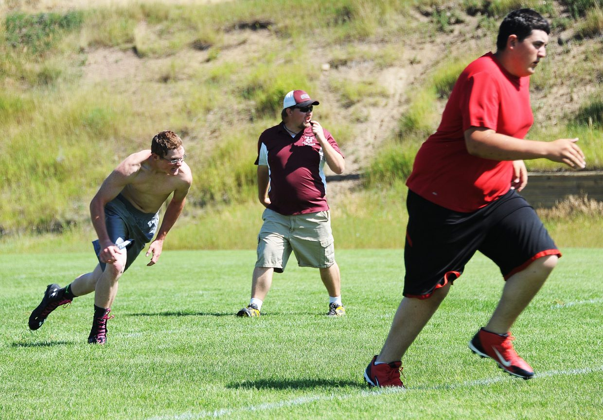 Soroco High School football coach Joe Keller watches a conditioning drill Tuesday in Oak Creek. Keller is stepping in as the program's coach while also serving as the school's athletic director.