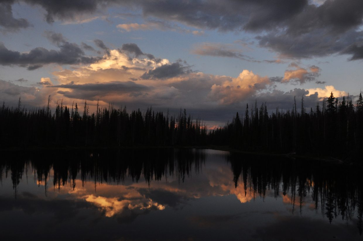 Dramatic clouds are reflected at sunset in the glassy waters of Summit Lake.
