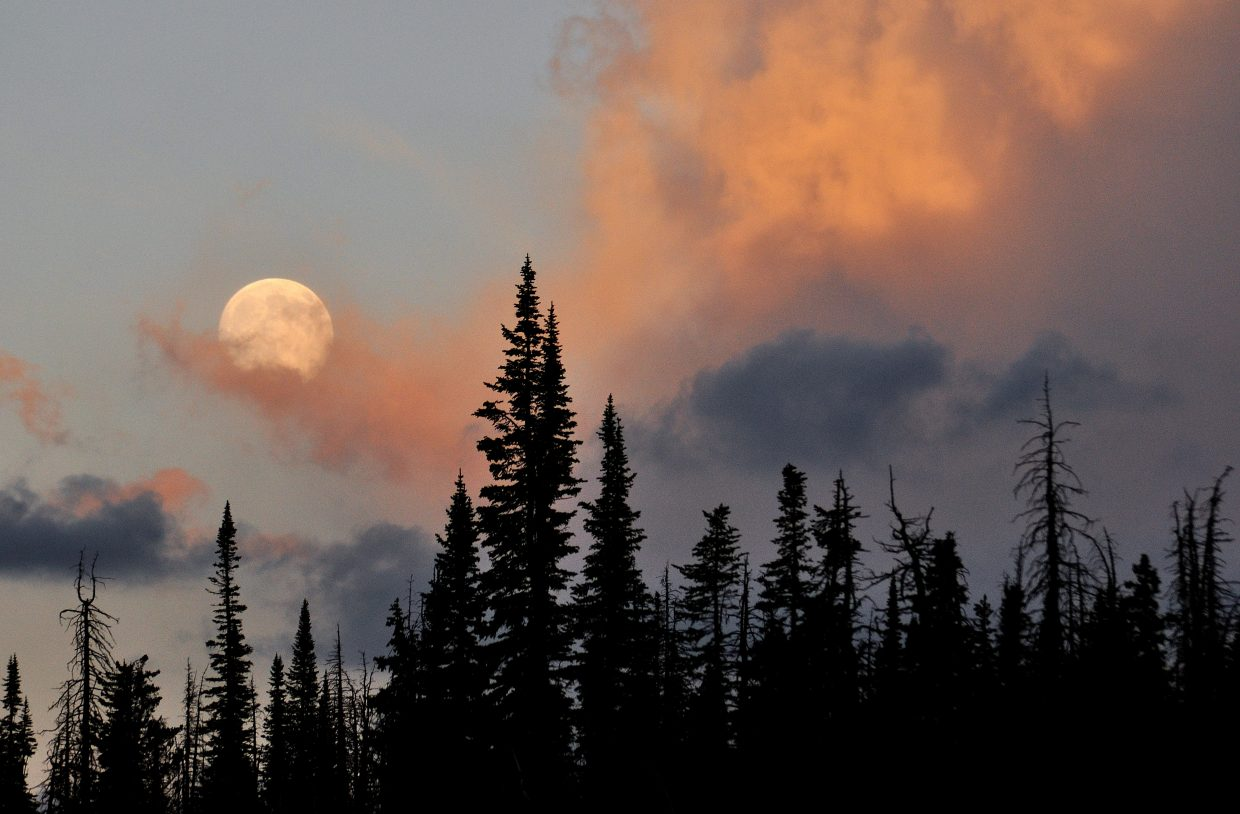 The moon rises above the clouds at sunset above Buffalo Pass.