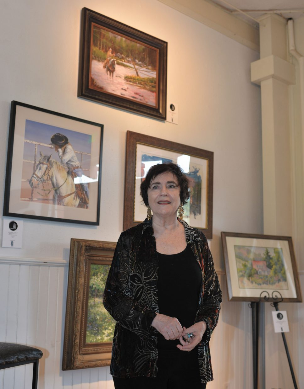 Judge Betsy Dillard-Stroud listens to a question at the Depot Art Center while standing in front of some of the top paintings in the Art Steamboat competition.