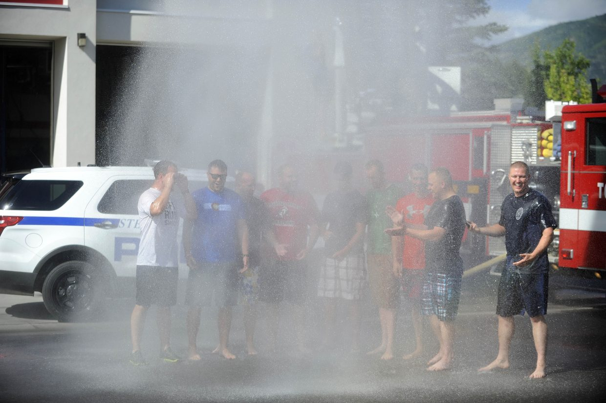Steamboat Springs Police Department officers get drenched with water Thursday at the Mountain Fire Station as part of a fundraiser for the Officer Down Memorial.