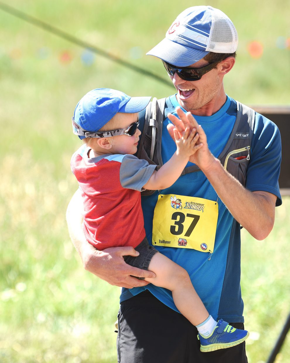 Gil Johnson, 21 months, gives his father, Nate Johnson, a high five Sunday after Nate finished the Steamboat Stinger trail marathon.