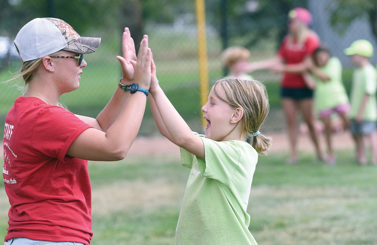 Oakley Yeager celebrates with Kids Adventure Club camp leader Heidi Fieldseth on Monday while playing a kickball game at Howelsen Hill. Summer camps will come to a close during the coming week as summer vacation winds down, and schools prepare to start a new academic year.