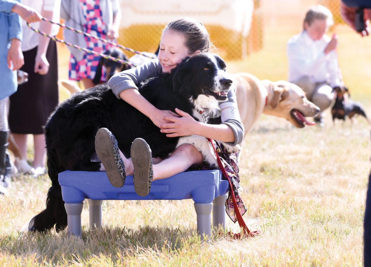Norah Pietras hugs her dog, Poncho, during the dog show Tuesday at the Routt County Fair in Hayden. The fair continues through Sunday.