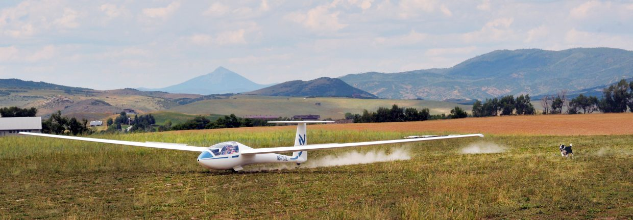 One of glider pilot Tom Wood's dogs chases him down the runway as he lands his glider at a private airfield west of Steamboat Springs.