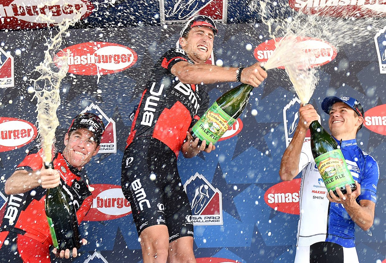 Brent Brookwalter, left and third in Stage 1, Taylor Phinney, the day's champ, and Kiel Reijnen, celebrate their results, spraying beer on each other and into the Steamboat Springs crowd Monday.