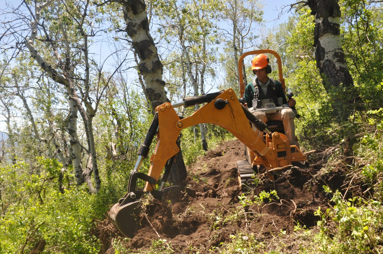 Marc Sehler drives a new singletrack trail-building machine as it clears brush and stumps from what will become the Morning Gloria trail on Emerald Mountain. The 4.25-mile singletrack trail opened to the public last week, about two months after construction started.