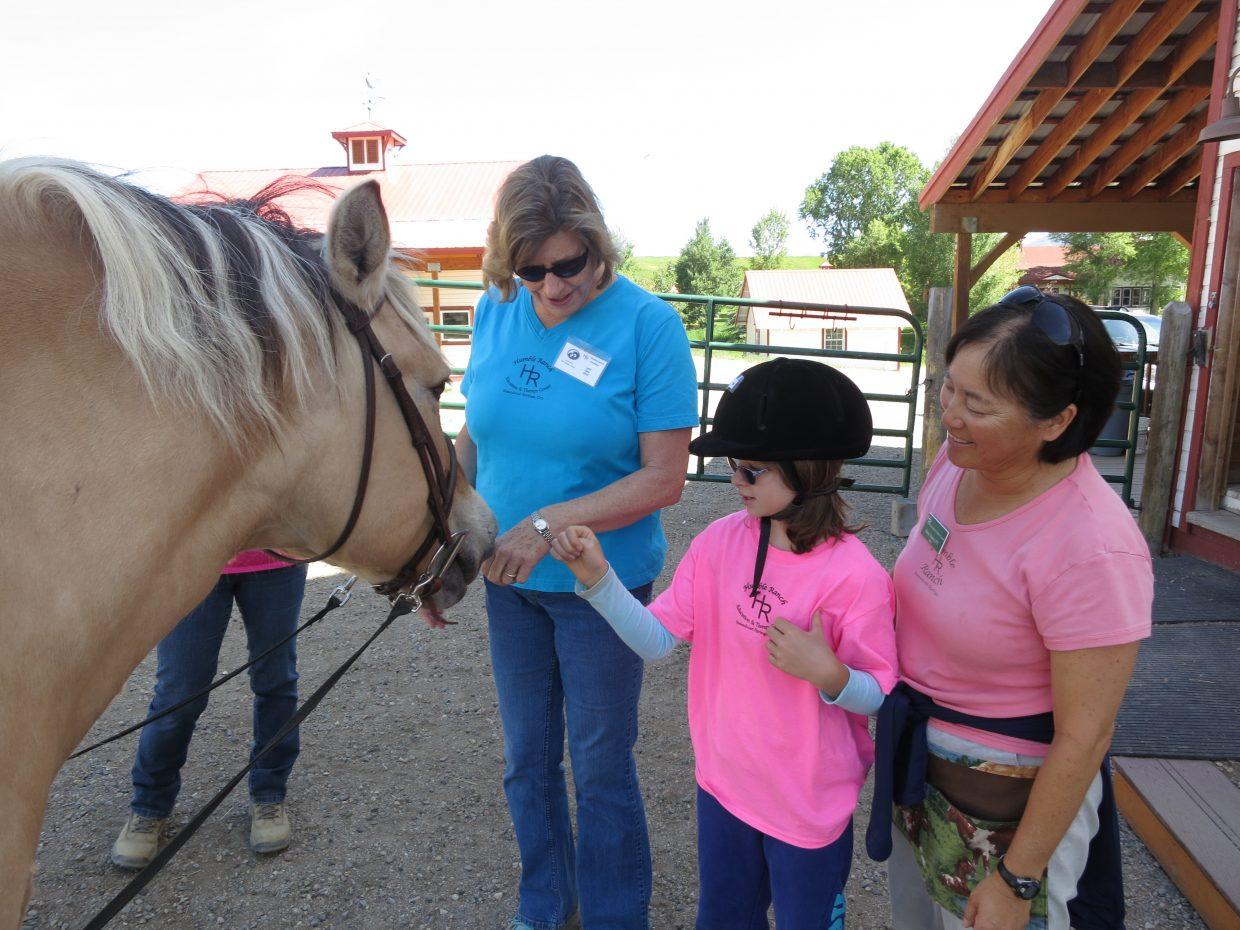 A client in the Humble Ranch Education & Therapy Center hippotherapy program greets her horse before beginning therapy.