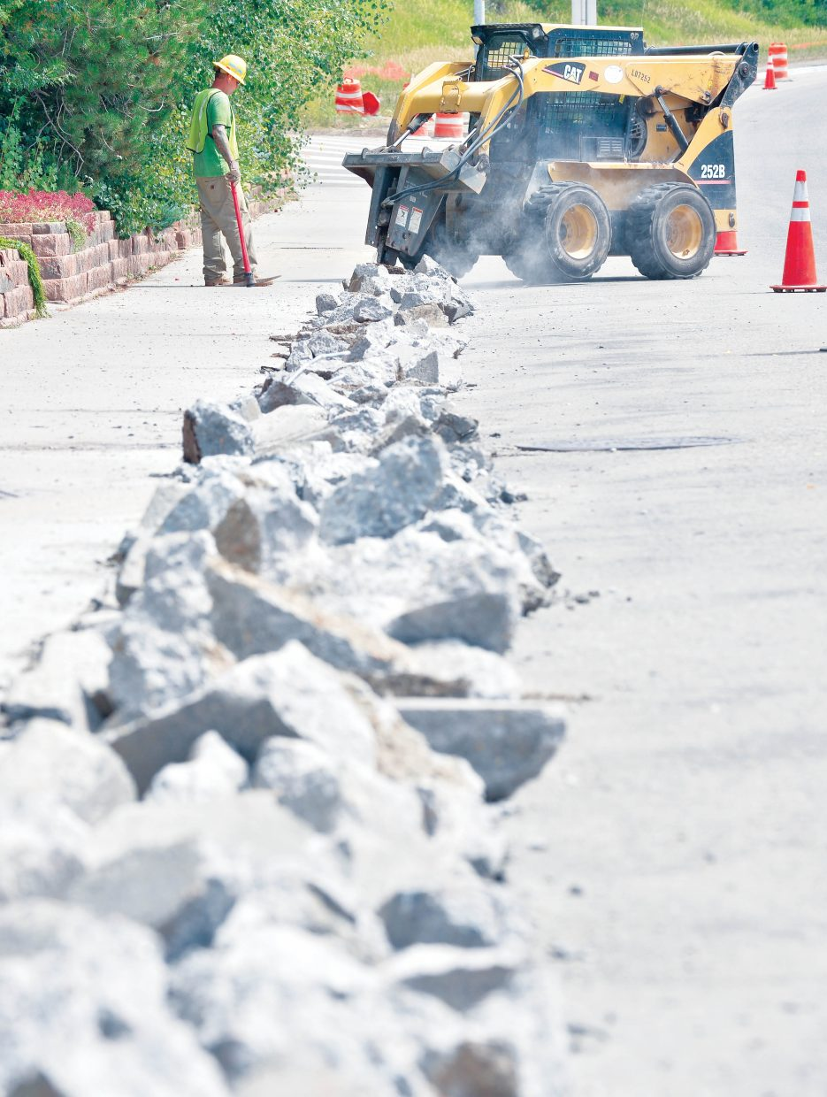 Construction workers Chase Davis and Josh Coulter (inside the bobcat) work to remove the old curves along west Lincoln Avenue on Tuesday afternoon. The curbs will be replaced before the highway is repaved later this fall.