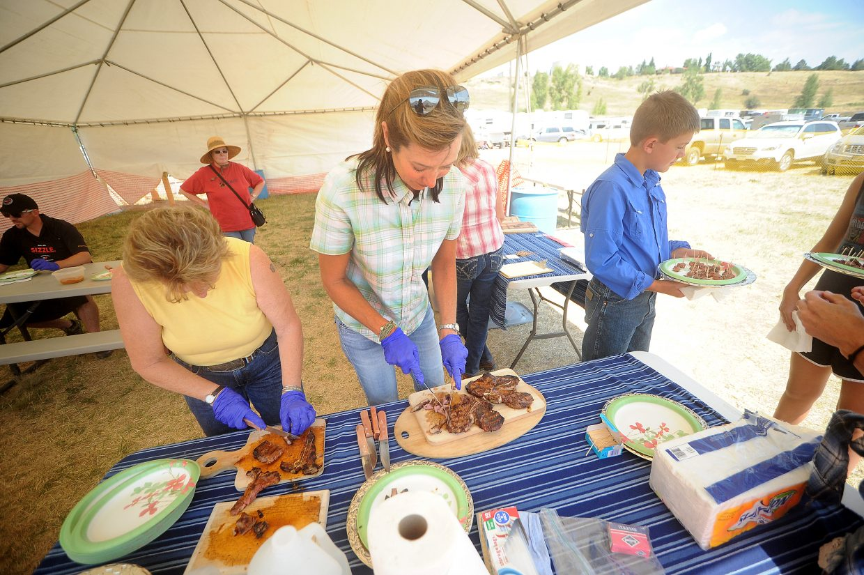 Routt County CattleWomen volunteers Sharon Clever, left, and Erika Murphy cut up steak to serve Friday during the Routt County Fair in Hayden.