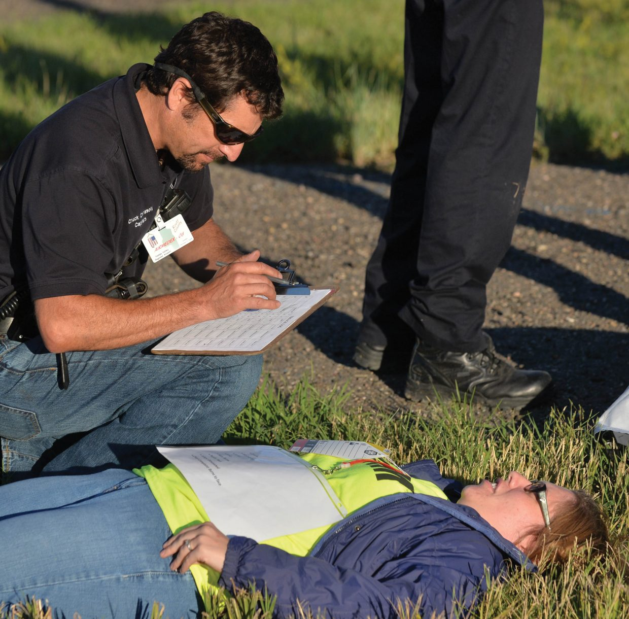 """Emergency responder Chuck Cerasoli checks on a """"victim"""" during a mass casualty drill at the Yampa Valley Regional Airport on Wednesday evening. The drill, which takes place once every three years, allows agencies from Oak Creek, Steamboat Springs, Hayden and Craig to run through procedures as though a commuter plane had crashed at the airport. The drill is designed to test procedures that are already in place, and give agencies a chance to practice the scenario as if a disaster had taken place."""