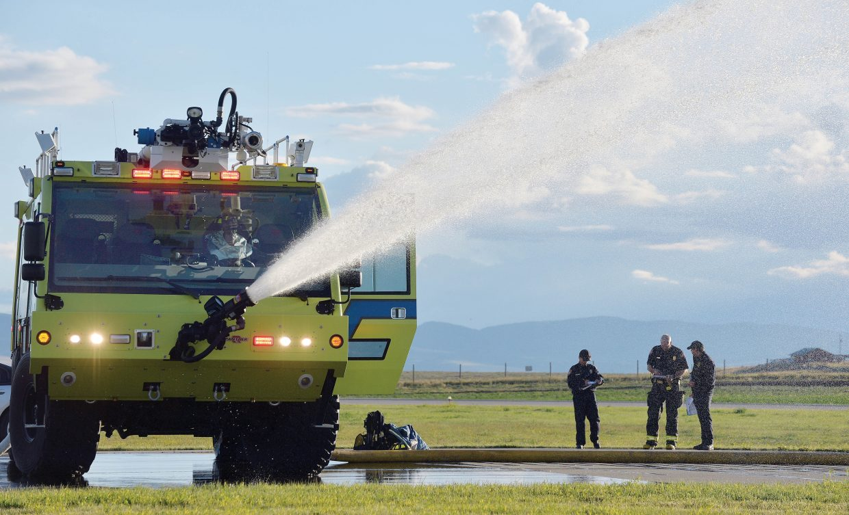 """Firefighters at the Yampa Valley Regional Airport use a specialized truck to extinguish a """"fire"""" during a mass casualty drill Wednesday evening. The drill, which takes place once every three years, allows agencies from Oak Creek, Steamboat Springs, Hayden and Craig to run through procedures as though a commuter plane had crashed at the airport. The drill is designed to test procedures that are already in place and give agencies a chance to practice the scenario as if a disaster had taken place."""