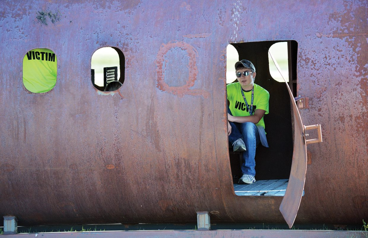 """""""Victim"""" Trace Fallon takes his place in the wreckage of a downed plane during a mass casualty drill at the Yampa Valley Regional Airport on Wednesday evening."""