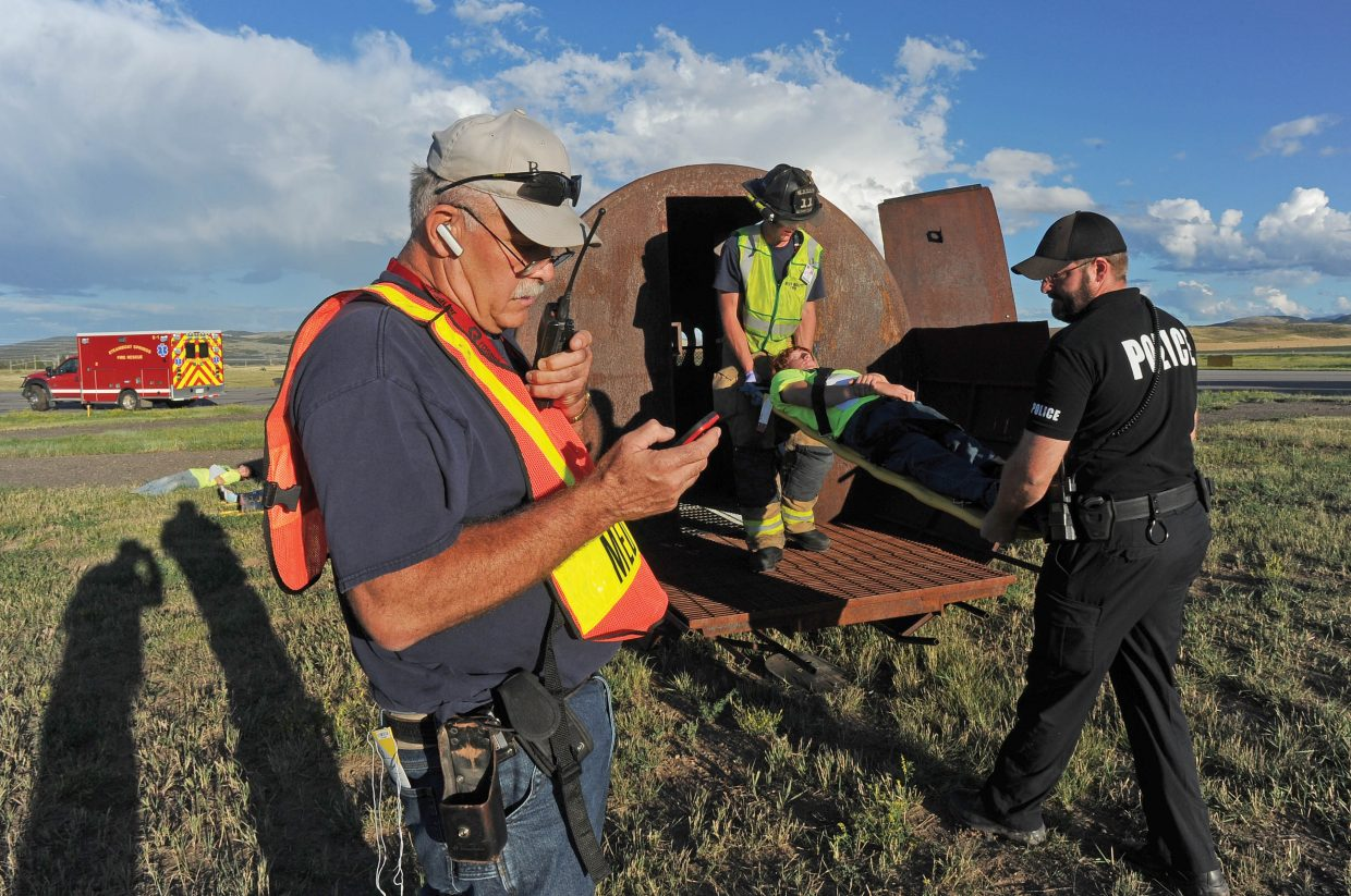 Emergency responder Bryan Rickman coordinates communication from the scene of a mock airplane crash during a mass casualty drill at the Yampa Valley Regional Airport on Wednesday evening. The drill, which takes place once every three years, allows agencies from Oak Creek, Steamboat Springs, Hayden and Craig to run through procedures as though a commuter plane had crashed at the airport. The drill is designed to test procedures that are already in place and give agencies a chance to practice the scenario as if a disaster had taken place.