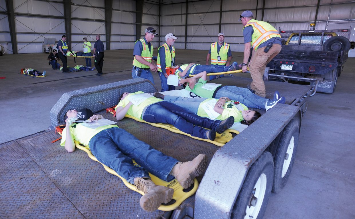 """Emergency responders unload """"victims"""" from a trailer used to transport them from the scene of a mock airline accident to a place where medical personnel could evaluate their conditions and make decisions about the urgency of their care during a mass casualty drill at the Yampa Valley Regional Airport. The drill, which takes place once every three years, allows agencies from Oak Creek, Steamboat Springs, Hayden and Craig to run through procedures as though a commuter plane had crashed at the airport. The drill is designed to test procedures that are already in place and give agencies a chance to practice the scenario as if a disaster had taken place."""