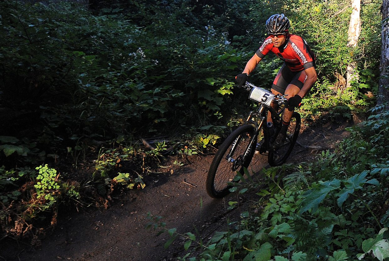 Brad Bingham flies down the Creekside trail on Wednesday night, chasing Alex Pond. He caught him and won a desperate race to the finish to win the men's pro/open division championship in the summer-long Steamboat Town Challenge mountain bike racing series.