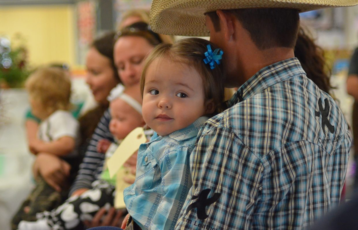 """Hurley Booco,16 months old, looks over her dad, Jake Booco's, shoulder during Sunday's Pretty Baby Contest at the Routt County Fair. Hurley was awarded """"best dressed for the rodeo"""" during the contest."""