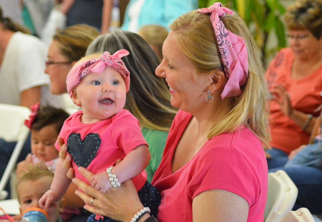 """Five-month-old Isabelle Rose Whitaker stands on her mom, Lilly Whitaker's, lap during Sunday's Pretty Baby Contest at the Routt County Fair. The mom and daughter duo tied for best """"dressed alike"""" pair."""