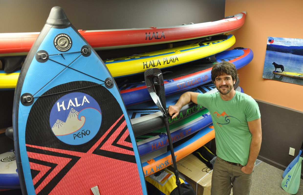 Hala Gear founder Peter Hall stands with an assortment of the stand-up paddleboards he has out in the market. The business has grown quickly during the past year.