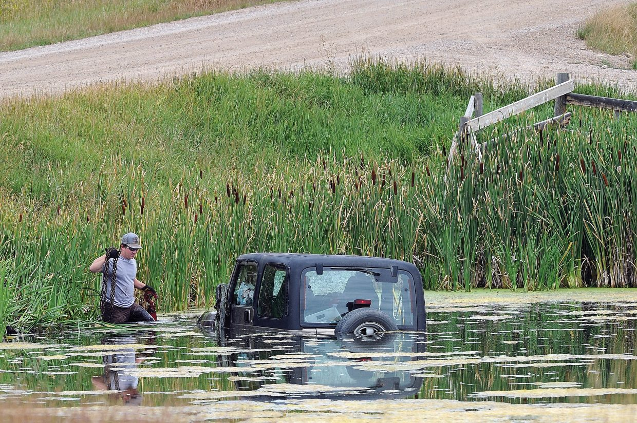Tow truck driver Lee Gittleton wades into a pond off of Routt County Road 44 on Friday morning while pulling a Jeep out of waist-deep water. Katlyn Furniball, a mail service contract worker, was driving the Jeep in the northbound lane when she caught the shoulder and was pulled down the embankment. The Jeep rolled one time before landing on its wheels in the pond. The Jeep was pulled out and taken to a local tow yard where, the mail was removed.