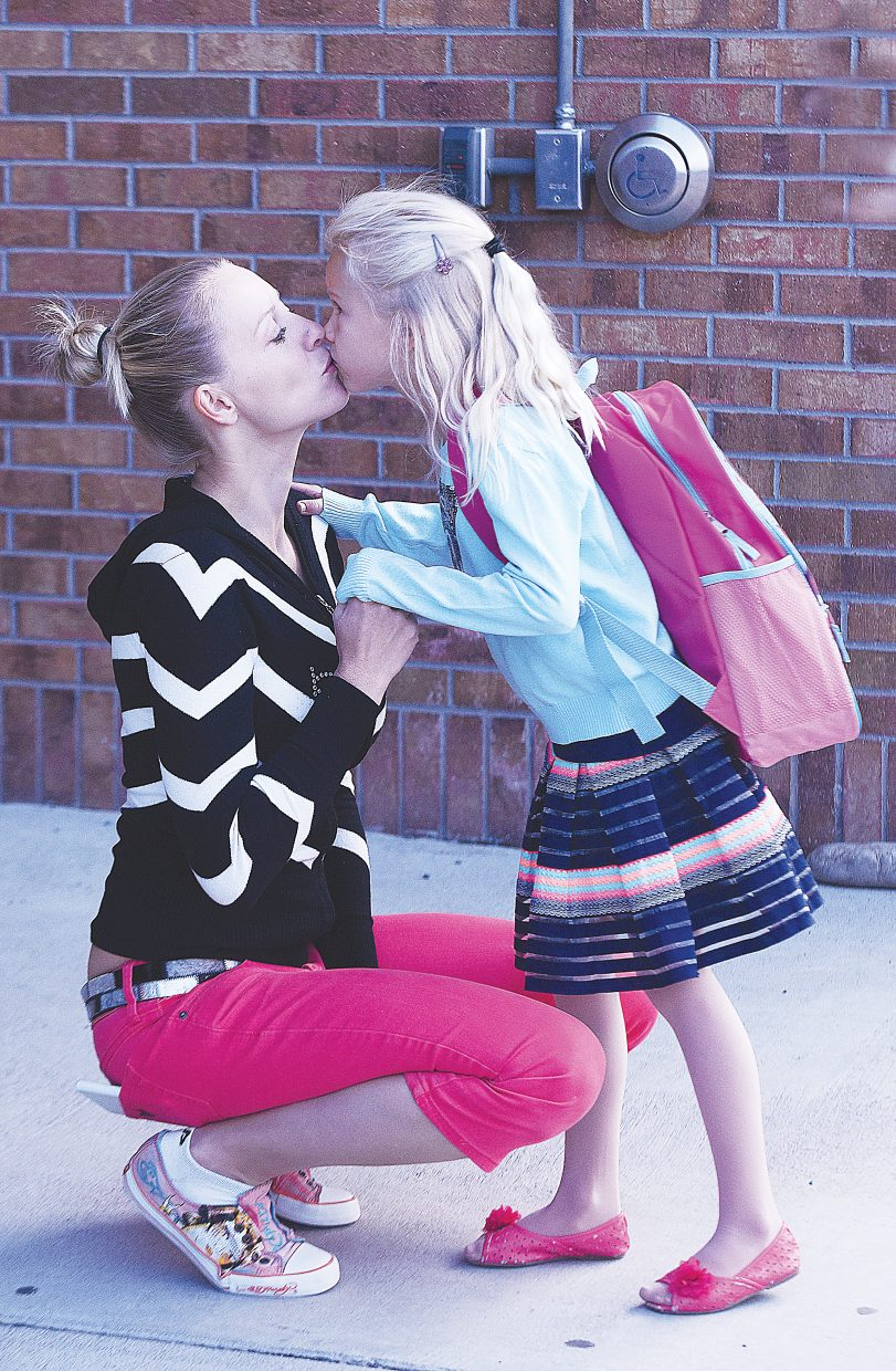Nikola Skoda gets a kiss from her daughter Dominika, 7, Tuesday morning at the entrance to Strawberry Park Elementary School in Steamboat Springs. Dominika was off to start her first day of second grade as students in Steamboat returned to class. The parade of first days of school will continue today as kindergarten students returns to class in Steamboat, and on Thursday, when students in Hayden return to class. Students at South Routt Schools went back to class Monday.
